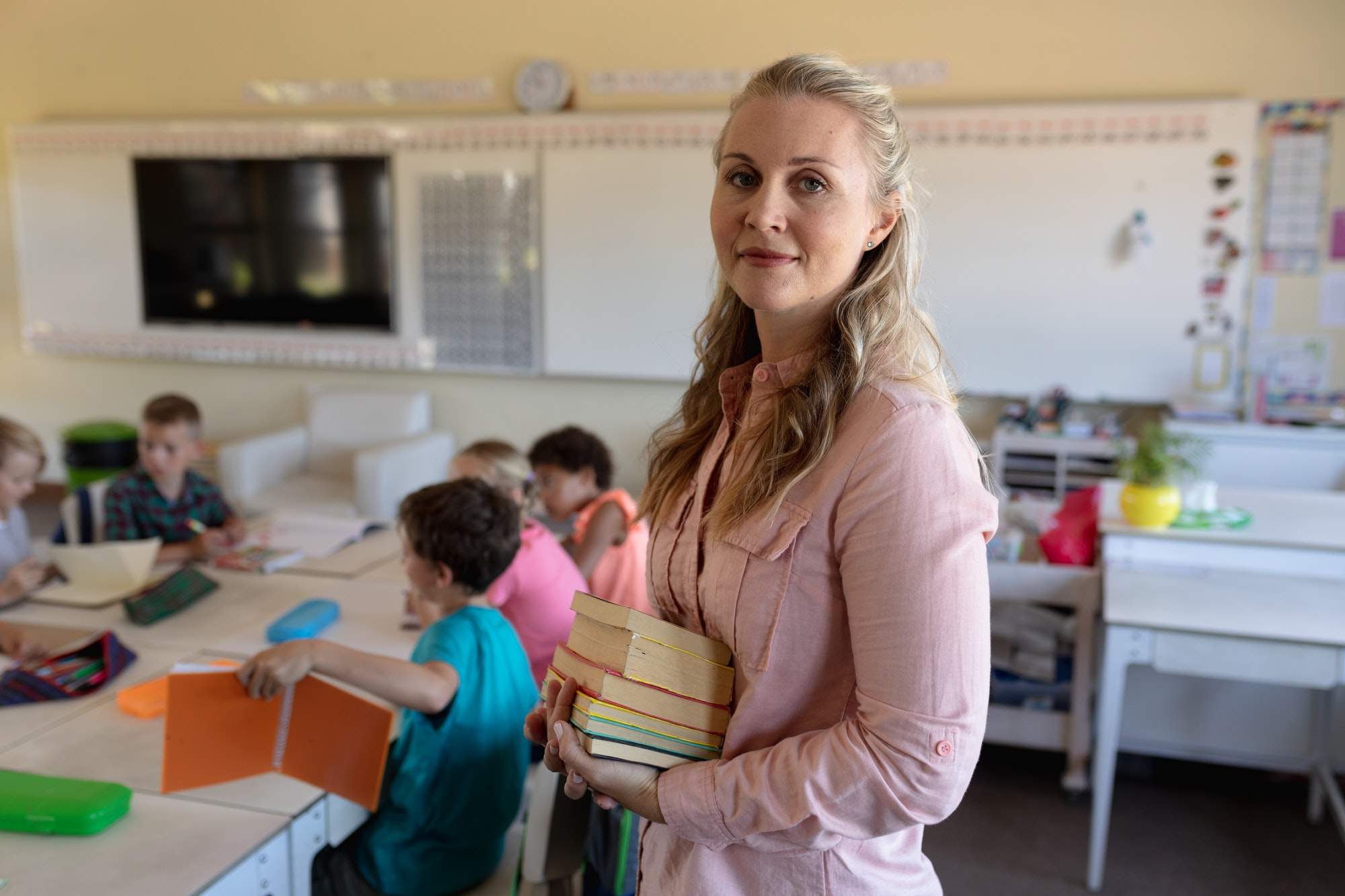 Female teacher with long blonde hair standing in a classroom