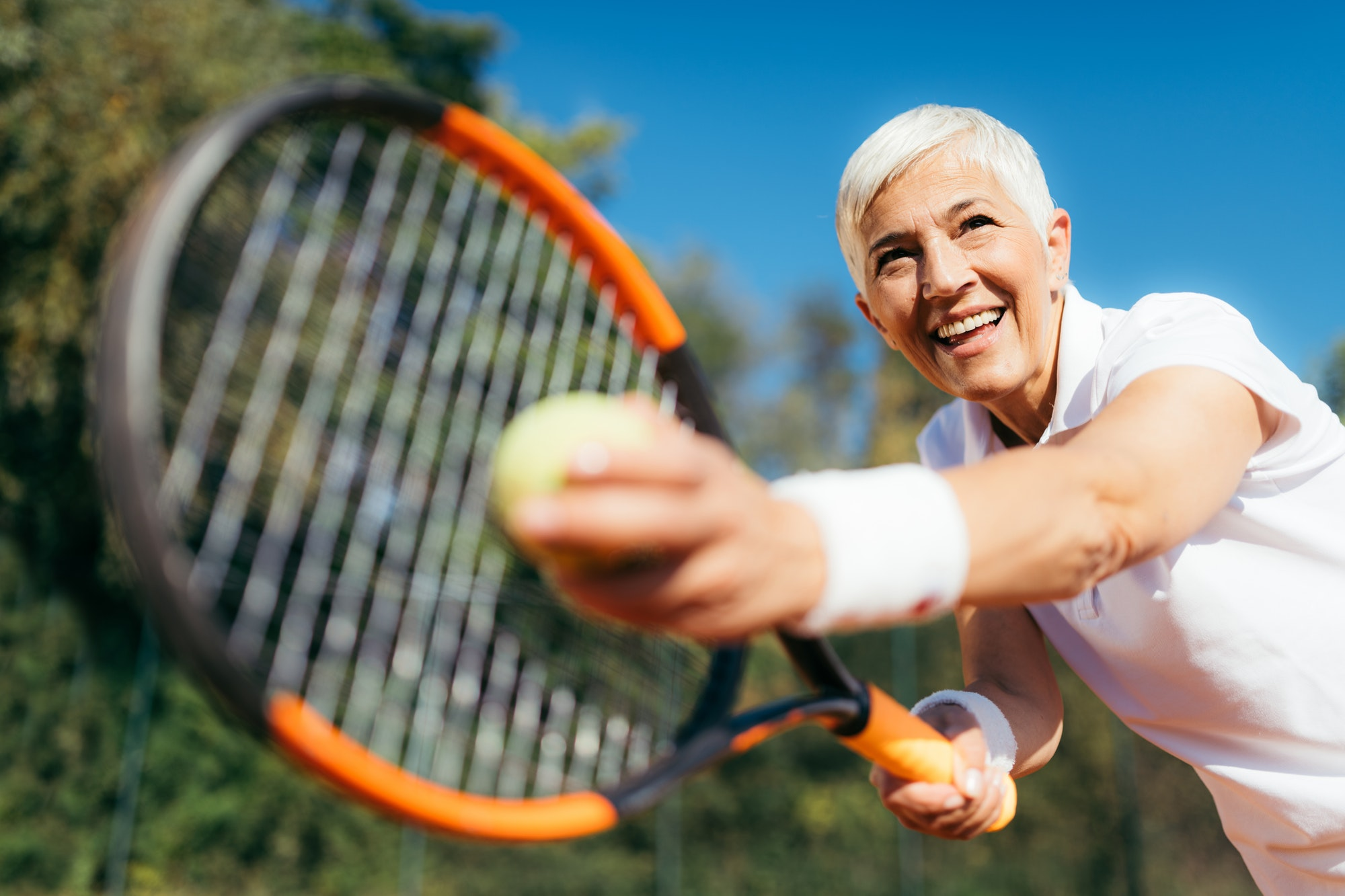 Senior Tennis – Pretty Mature Woman Serving Ball in Tennis