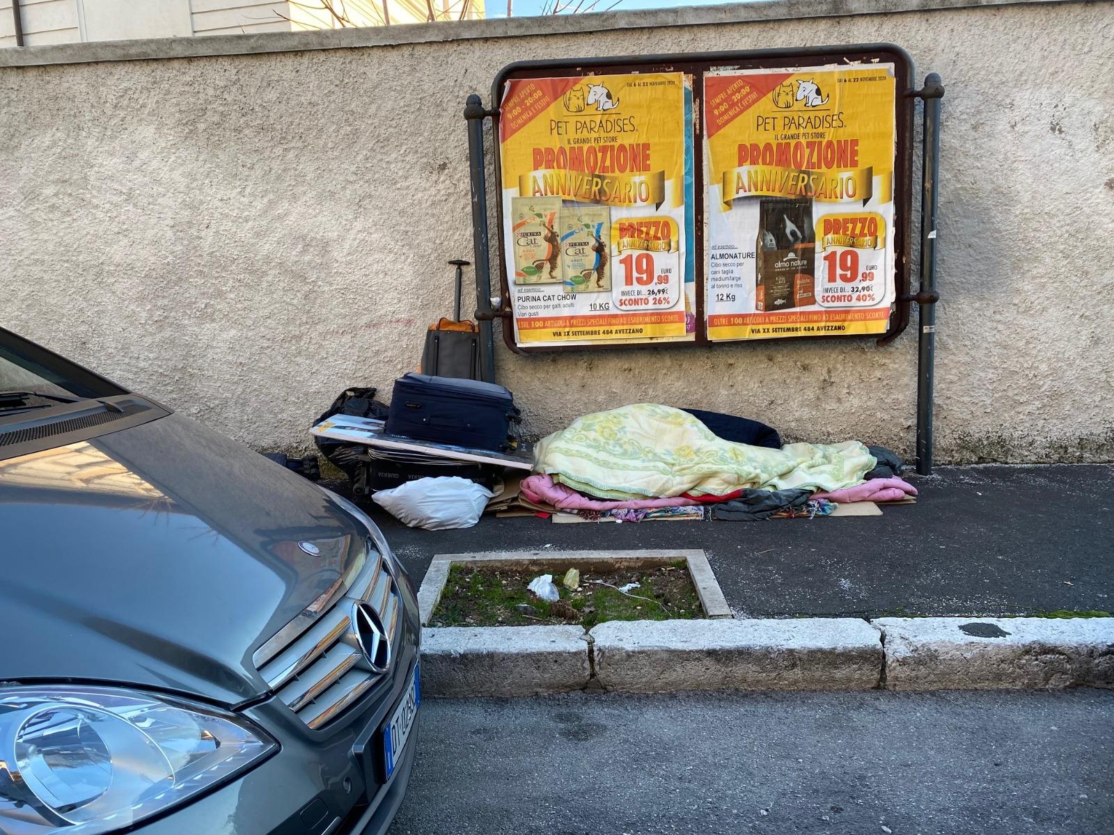 Da sotto i portici al marciapiede, l'immagine del clochard di Avezzano che dorme in via Trieste