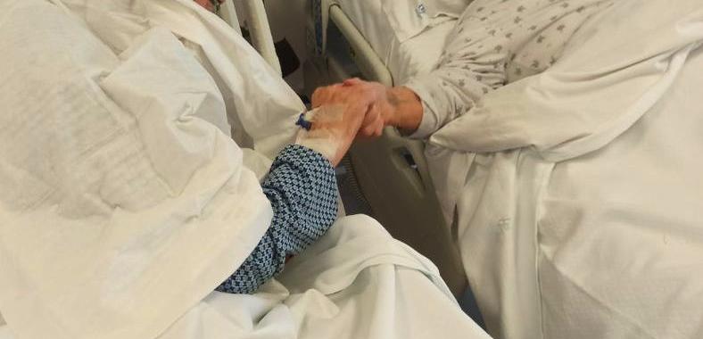 Due anziani coniugi si tengono per mano nel reparto Covid-19 in cui sono ricoverati, la foto commuove il web