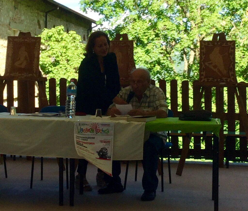 La scrittrice Maria Assunta Oddi con l'artista Ascenzo Bianchi nella verde cornice della selva del Convento francescano illustrano la mostra ai presenti